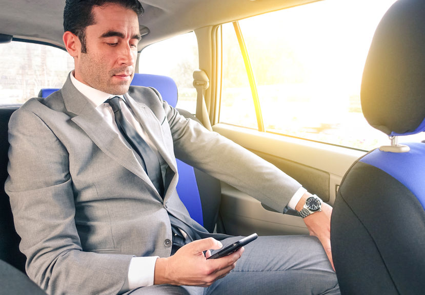 36996002 - young handsome businessman sitting in taxi cab while texting sms with smartphone - business concept with modern man using smart phone - soft vintage editing with artificial sunlight from the window